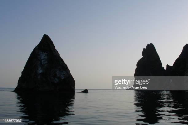 rock formations rising out of water at night, black sea, crimean coast - argenberg stock-fotos und bilder