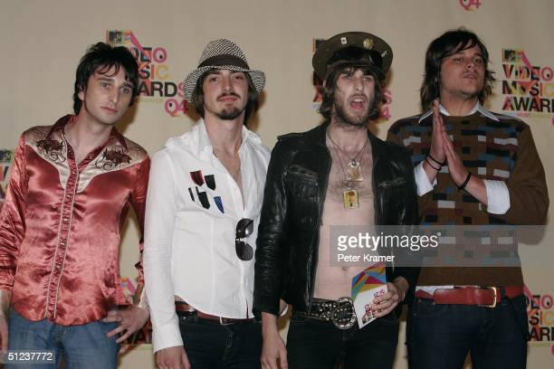 Rock group band members Cameron Muncey Chris Cester Nic Cester and Mark Wilson of Jet pose after winning the award for Best Rock Video in the press...