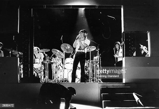 Rock group Pink Floyd rehearsing at Earls Court prior to a concert Singer Roger Waters wears headphones at the front of the stage Original...