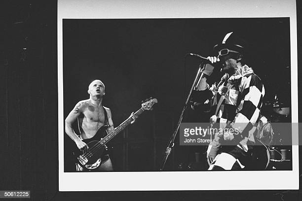 Rock group Red Hot Chili Peppers bass guitarist Flea, clad only in skivvies, playing on stage w. Singer Anthony Kiedis who sports white-framed...