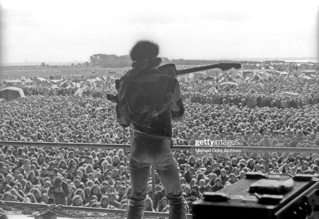 Rock Guitarist Jimi Hendrix Performs Onstage Plucking The Strings Of His Fender Stratocaster Electric Guitar With