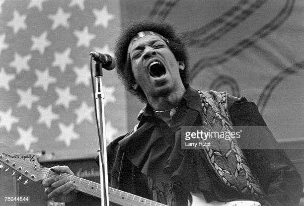 Rock guitarist Jimi Hendrix performs onstage with his Fender Stratocaster electric guitar in front of an American Flag on September 15 1968 in...