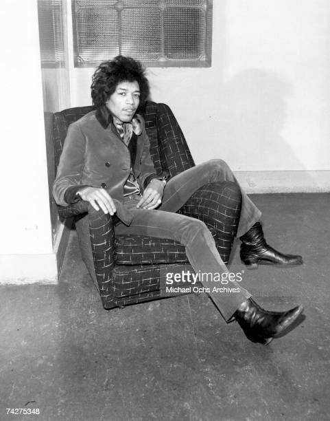 Rock guitarist Jimi Hendrix poses for a portrait sitting in a chair in 1966 in London England