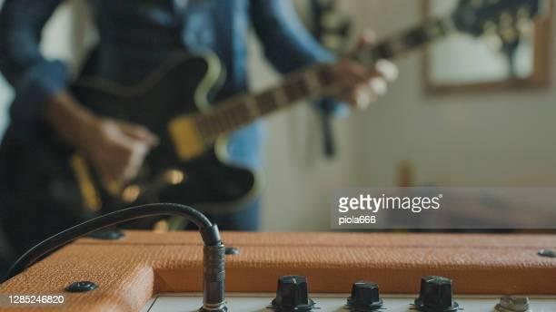 covid-19ロックダウン中に自宅でギターを弾くロックギタリスト - アンプ ストックフォトと画像