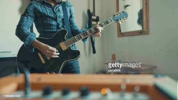 rock guitarist playing guitar at home, alone during covid-19 lockdown - musician stock pictures, royalty-free photos & images
