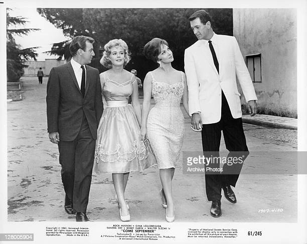 Rock Hudson and Gina Lollobrigida walking with another couple in a scene from the film 'Come September' 1961