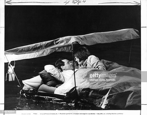 Rock Hudson out on bed raft with Paula Prentiss in a scene from the film 'Man's Favorite Sport' 1964