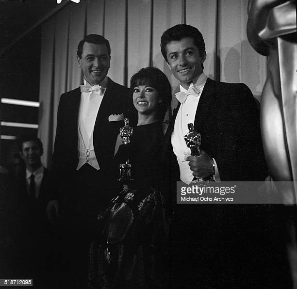 "Rock Hudson stands with Rita Moreno and George Chakiris with their Oscar during the Academy Awards after winning for ""West Side Story"" in Los..."