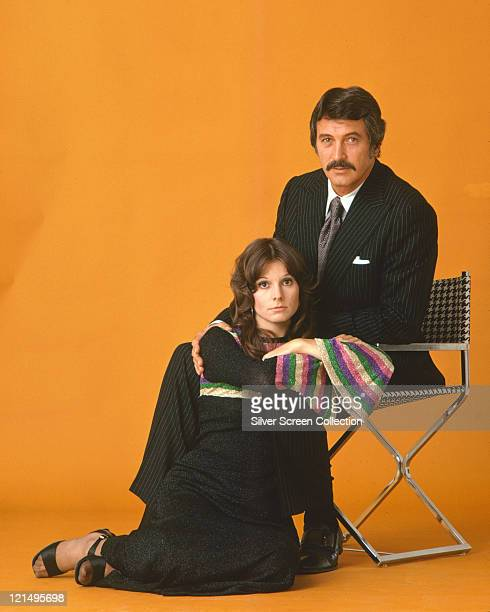 Rock Hudson US actor sits in a deckchair with Susan Saint James US actress laying at his feet on the floor in a studio portrait against an orange...