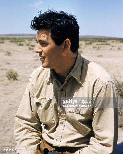 Rock Hudson US actor wearing a beige shirt sitting against a barren landscape in a publicity portrait issued for the film 'Giant' USA 1958 The drama...