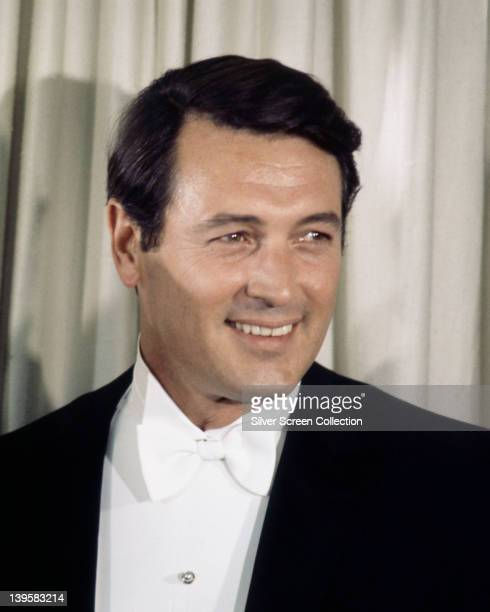 Rock Hudson US actor wearing a black tuxedo with a white shirt and white bow tie attending the 36th Academy Awards ceremony at the Santa Monica Civic...