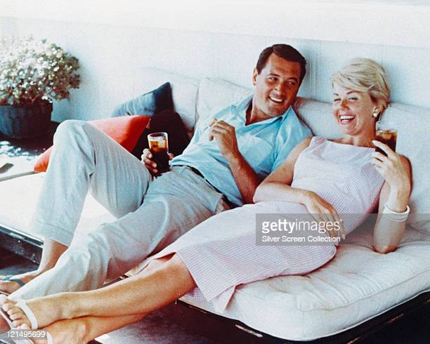 Rock Hudson US actor wearing white trousers and a light blue shortsleeved shirt and Doris Day US singer and actress in a pink gingham dress both...