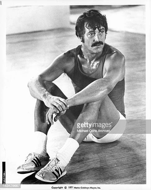 Rock Hudson wearing shorts and a tee shirt sitting in a gymnasium with sweat beads on his chest in a scene from the film 'Pretty Maids All In A Row',...