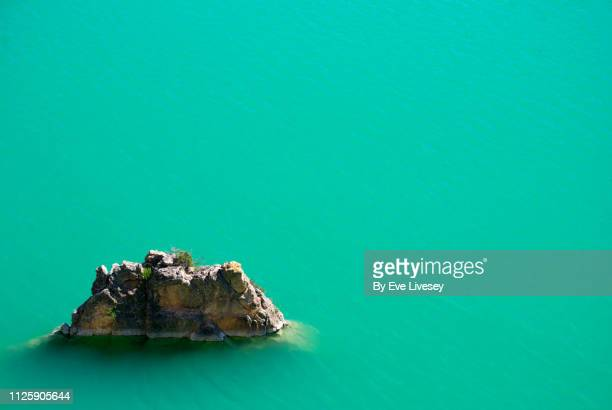 rock in a turquoise lake - emerald green stock pictures, royalty-free photos & images