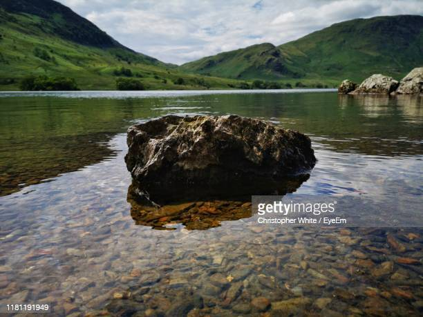 rock in lake against sky - cockermouth stock pictures, royalty-free photos & images