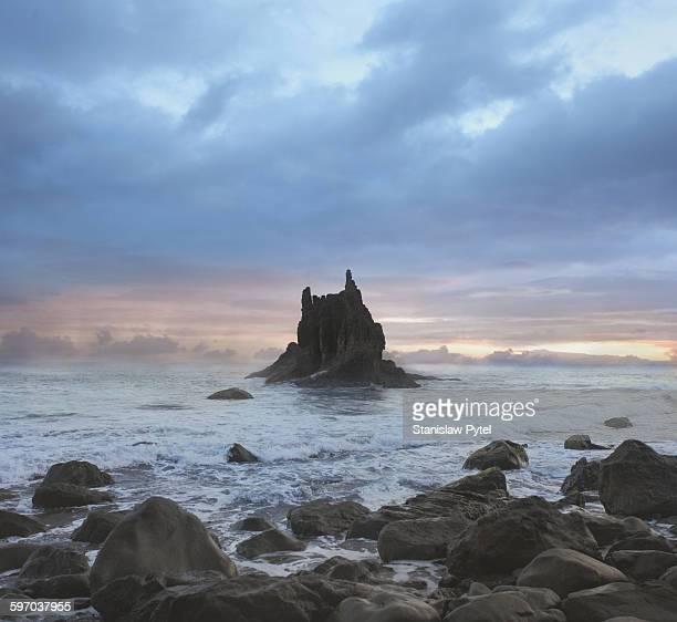 Rock in ocean against stormy sky
