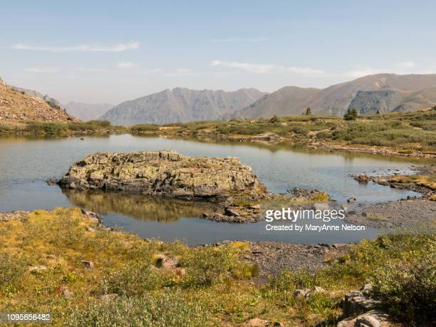 rock in the middle of a mountain lake - mary lake stock photos and pictures