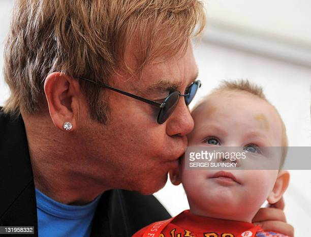 """Rock legend Sir Elton John kisses little Lev, a patient of a specialized orphanage for HIV-positive children after the first results of the """"Children..."""