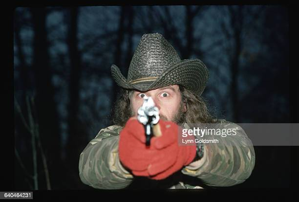 Rock musician and hunting enthusiast Ted Nugent wears camouflage clothing and aims at the camera