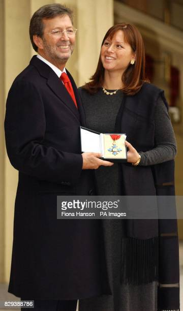 Rock musician Eric Clapton with his wife Melia at Buckingham Palace London after receiving a CBE for services to music from the Prince of Wales