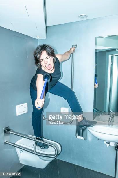 rock musician holding toilet brush and singing in bathroom - human toilet stock-fotos und bilder