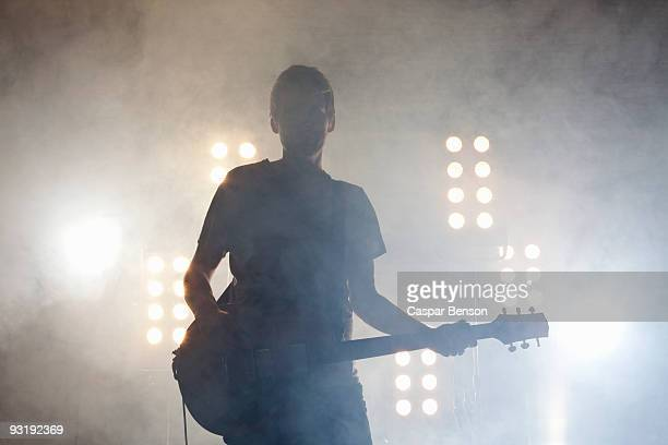 a rock musician playing a guitar on a stage - popmuzikant stockfoto's en -beelden