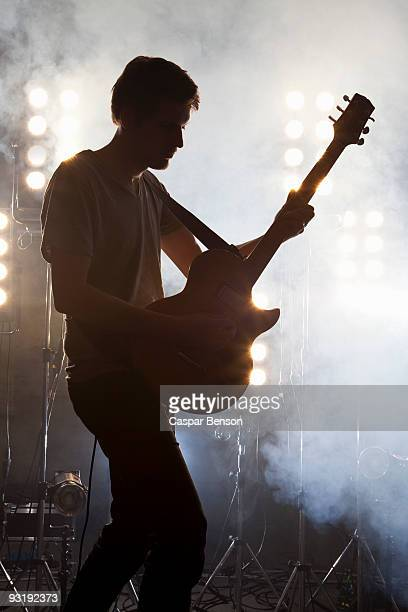 A rock musician playing a guitar on a stage