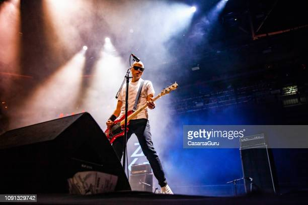 rock musician playing electric guitar on stage - filter band stock photos and pictures