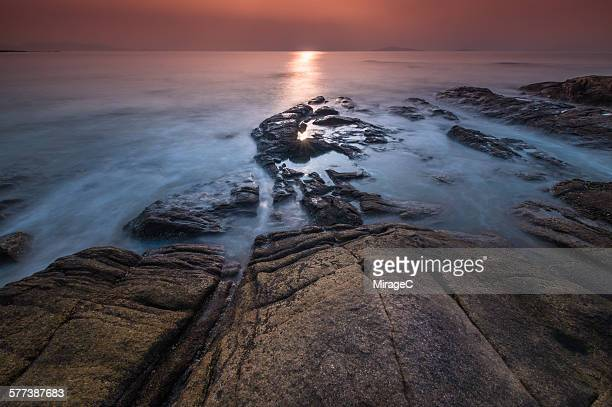 Rock on beach with flowing water waves sunlight