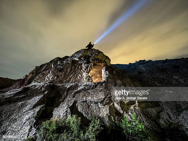 Rock on the top of a mountain with a refuge excavated in his interior and a man with a lantern.