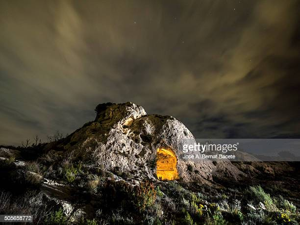 Rock on the top of a mountain with a refuge excavated in his interior during the night