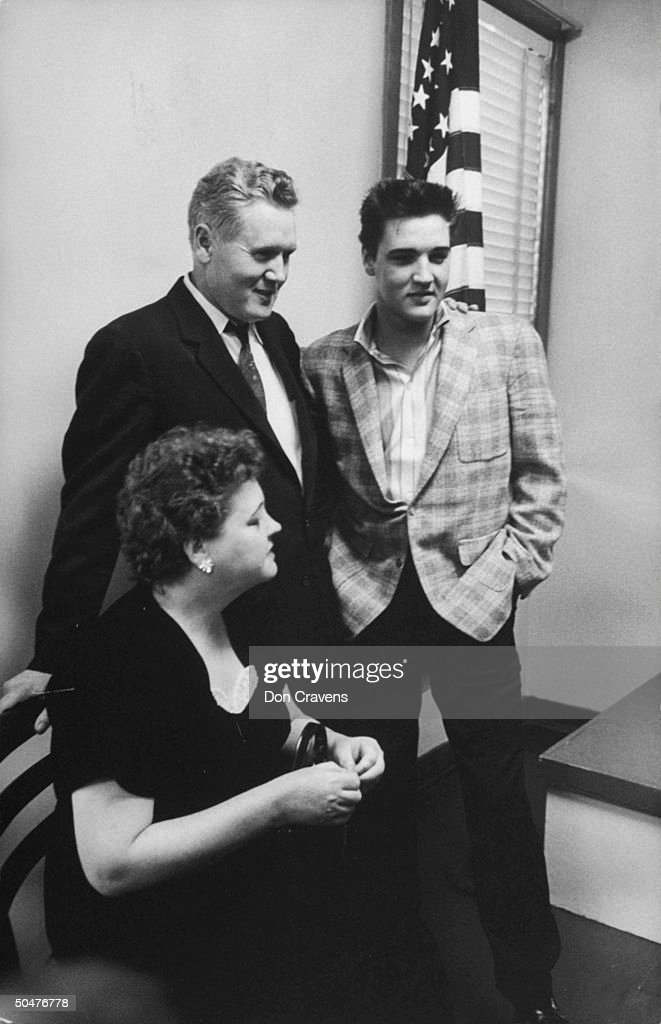 Rock & Roll singer Elvis Presley (R) standing next to his dad Vernon as his mom Gladys sits nearby while they wait w. him before he is processed at the Army Induction Center.