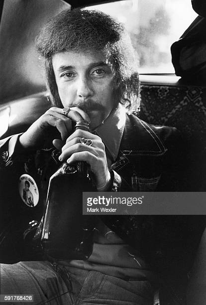 Rock Roll songwriter and record producer Phil Spector nurses a bottle of liquor while being driven through the Hollywood Hills after a recording...