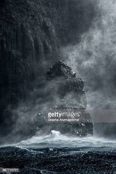 Rock sea stack with misty sea spray