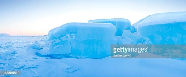 Rock shaped ice chunks shimmer blue at sunset