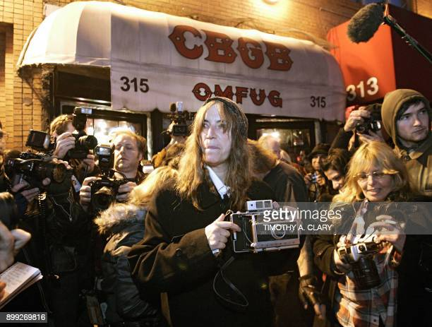Rock star and poet Patti Smith comes outside to take pictures of CBGB New York's most famous punk bar on its closing night 15 October 2006 after 33...