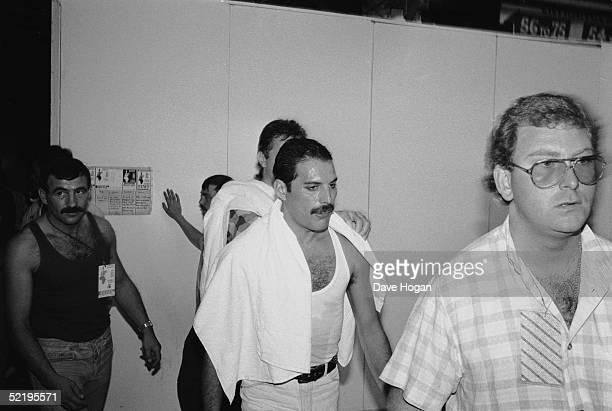 Rock star Freddie Mercury backstage at the Live Aid concert at Wembley, 13th July 1985. On the left is his boyfriend Jim Hutton.