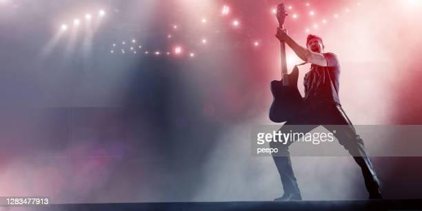 rock star che tiene la chitarra sul palco - musicista di musica pop foto e immagini stock