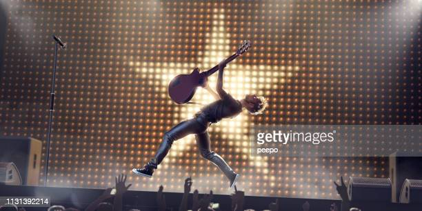 rock star in mid air jump with guitar on stage - gitarre stock-fotos und bilder