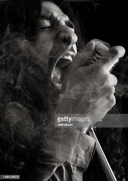 Rock star singing on old fashioned microphone in smoke