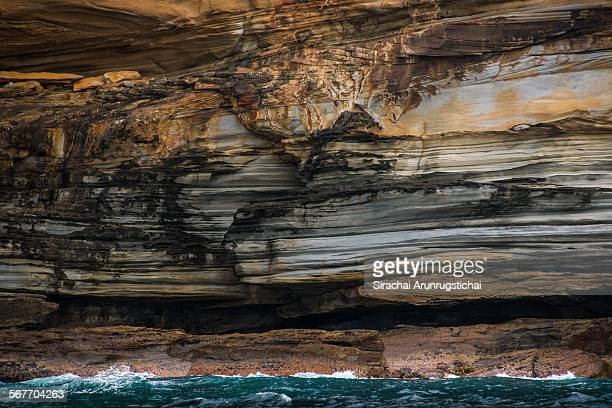 rock strata on a cliff by the sea - rock strata stock pictures, royalty-free photos & images