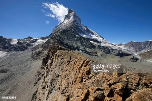 Rock strata that are snow covered most of the year. This ridge leads up to the Matterhorn. Clouds hang on to summit of the Matterhorn.