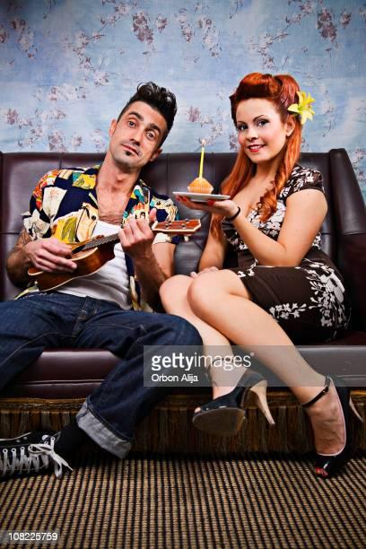 Rockabilly Couple Playing Ukelele and Holding Cupcake with Candle