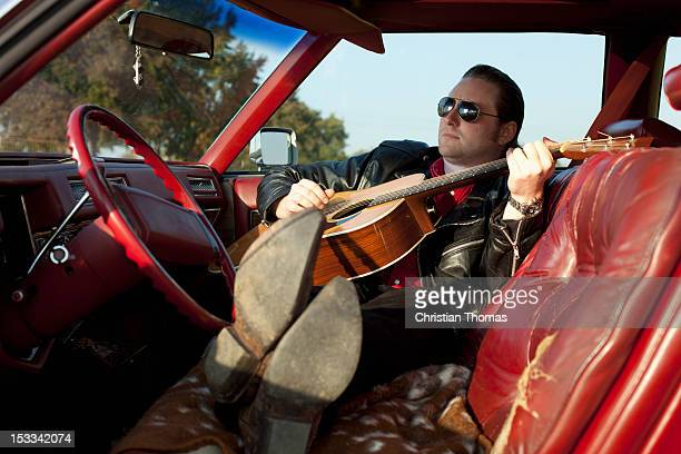A rockabilly guy playing an acoustic guitar while sitting in his vintage car