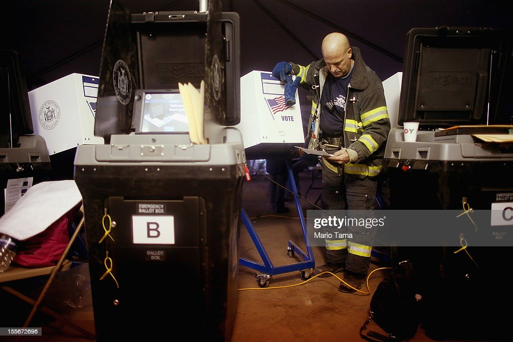 Rockaway resident and New York City firefighter Terence O'Donnell stands on sand among voting machines as he prepares to vote in a makeshift tent set up as a polling place at Scholars' Academy, PS 180, in the Rockaway neighborhood on November 6, 2012 in the Queens borough of New York City. The Rockaway section of Queens was one of the hardest hit areas and O'Donnell's home is damaged. Many voters in New York and New Jersey are voting at alternate locations in the presidential election due to disruption from Superstorm Sandy.