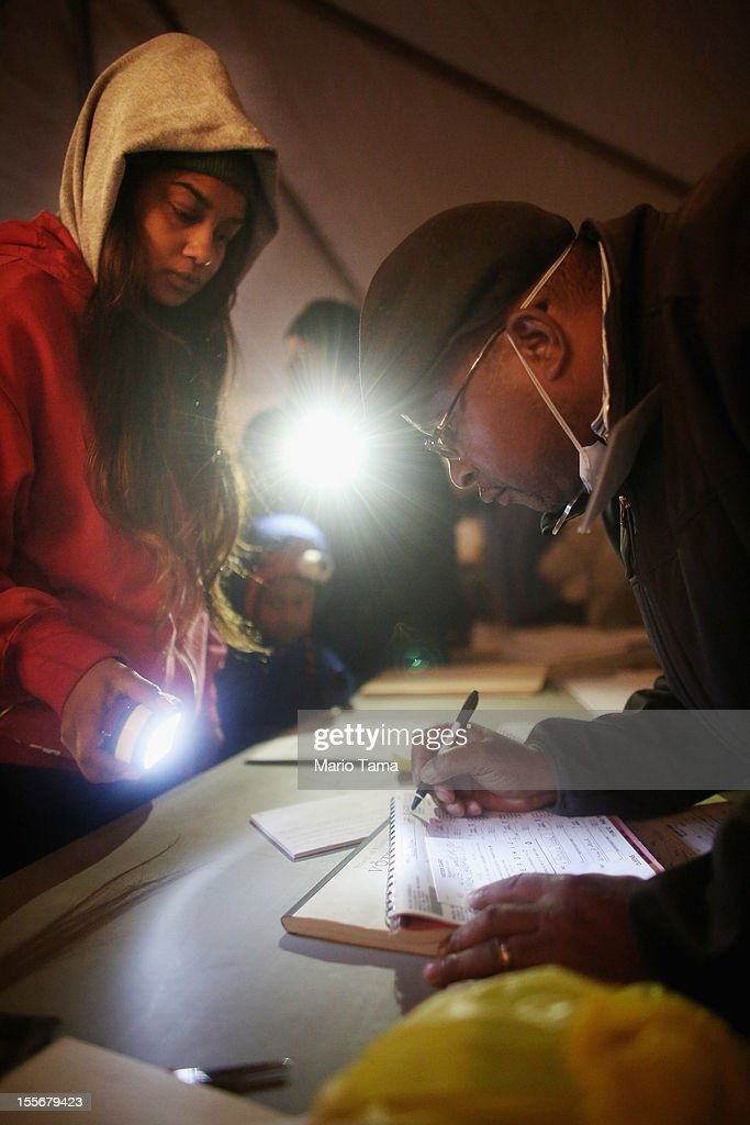 Rockaway resident Sheresa Walker (L) uses a flashlight as poll worker Lloyd Edwards assists before voting in a makeshift tent set up as a polling place at Scholars' Academy, PS 180, in the Rockaway neighborhood on November 6, 2012 in the Queens borough of New York City. The Rockaway section of Queens was one of the hardest hit areas. Many voters in New York and New Jersey are voting at alternate locations in the presidential election due to disruption from Superstorm Sandy.