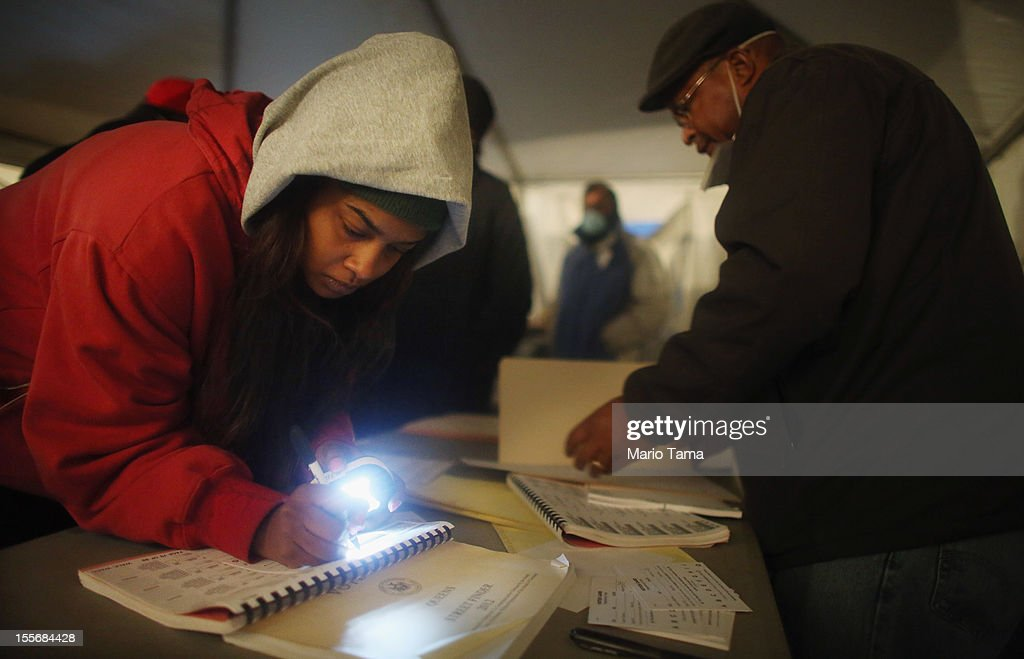 Rockaway resident Sheresa Walker (L) uses a flashlight as poll worker Lloyd Edwards works before voting in a makeshift tent set up as a polling place at Scholars' Academy, PS 180, in the Rockaway neighborhood on November 6, 2012 in the Queens borough of New York City. The Rockaway section of Queens was one of the hardest hit areas. Many voters in New York and New Jersey are voting at alternate locations in the presidential election due to disruption from Superstorm Sandy.