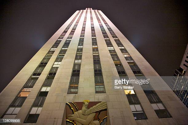 30 Rockefeller Plaza exterior with mural above entrance, Lee Lawrie's 'Wisdom, Light and Sound' at night, New York, NY