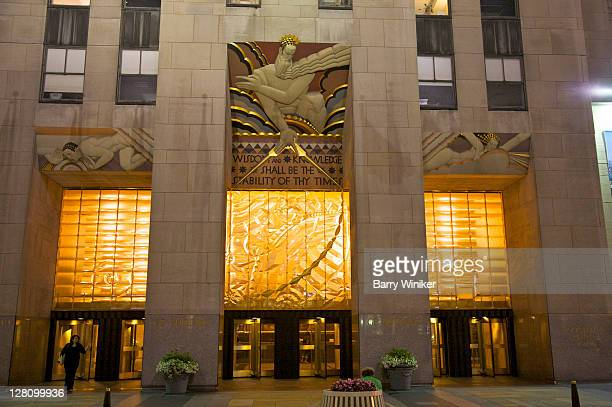 30 rockefeller plaza exterior with mural above entrance, lee lawrie's 'wisdom, light and sound' at night, new york, ny - rockefeller centre stock pictures, royalty-free photos & images