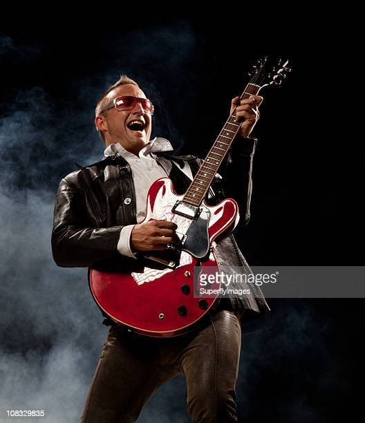 Rocker Man Plays Electric Guitar and Sings. Smoky Black Background.
